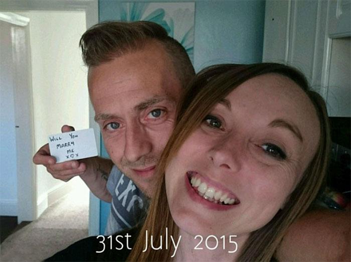 Chico proponiendole matrimonio a una chica con una tarjeta mientras se toman una selfie en el sofá