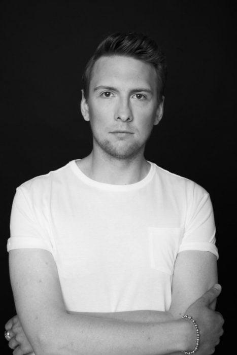 comediante Joe Lycett usando una camisa blanca durante una sesión de fotos