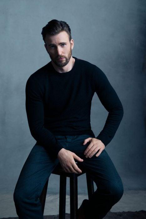Chris Evans sentado en un banco posando para una fotografía
