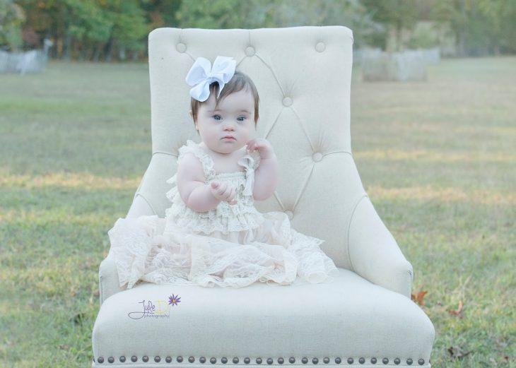 Fotógrafa Julie Wilson capturando la belleza de un niña con síndrome de down sentada en una silla