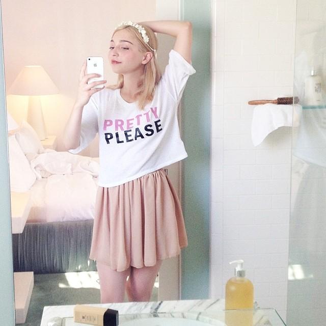 Amalia Ulman vestida con falda rosa y blusa blanca tomándose una fotografía frente a un espejo