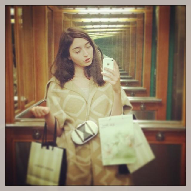 Amalia Ulman tomándose una selfie frente a un espejo mientras carga bolsas en sus manos