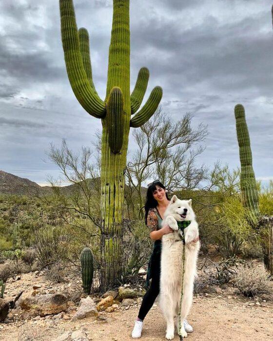 Lauren Urasek sosteniendo a un perro en un desierto