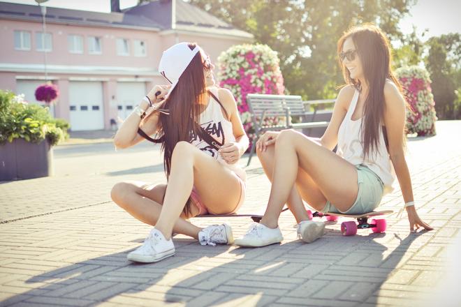 Chicas sentadas sobre unas patinetas conversando