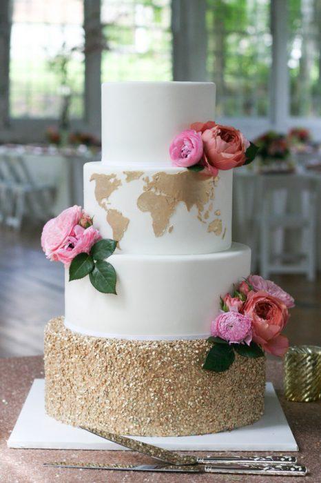 Pastel de bodas con un mapa dorado en uno de los pisos