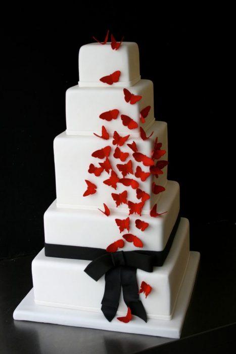 Pastel de boda de color blanco con un moño negro y mariposas de color rojo