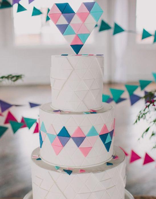 Pastel de bodas de color blanco con rombos de corazónes en colores