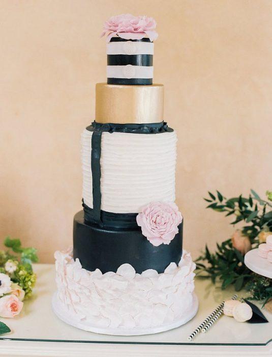 Pastel de bodas en color blanco, negro y dorado con flores en color rosa bebé