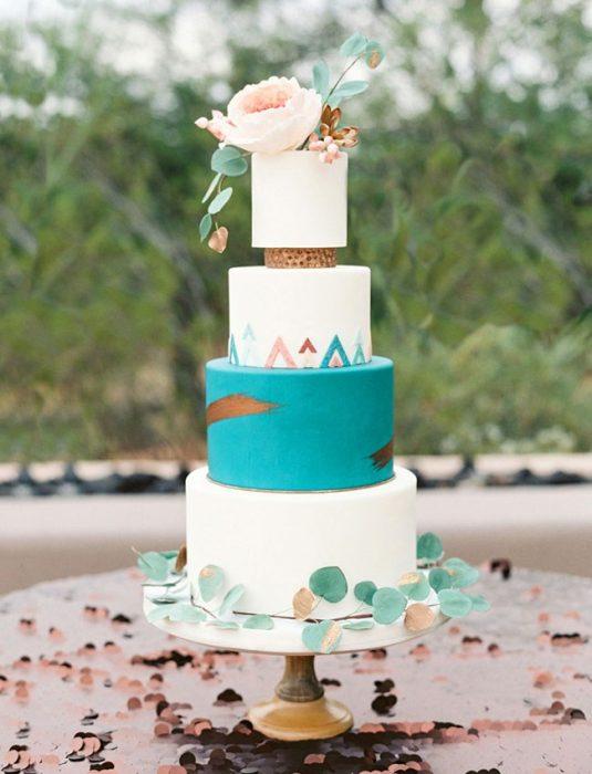 Pastel de bodas en color blanco con azul y en la punta flores de color blanco