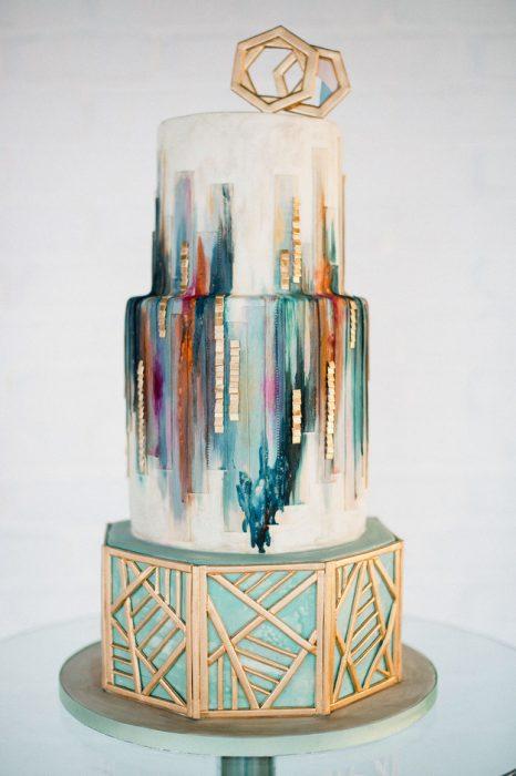 Pastel de bodas en color azul con blanco y pintura de distintos colores con rombos dorados en la parte superior