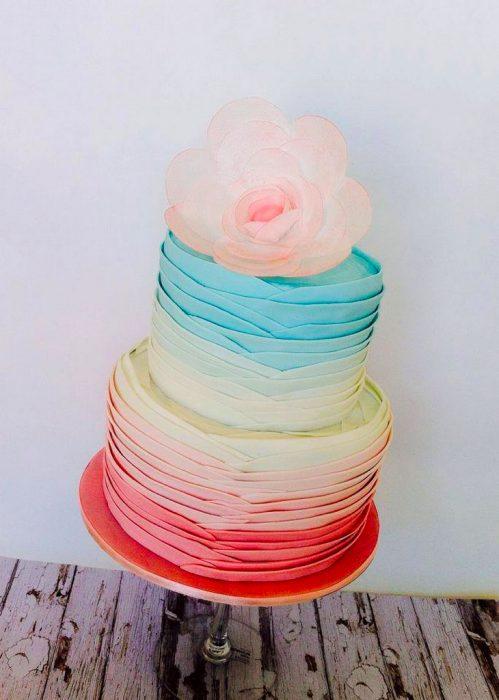 Pastel de distintos colores con una flor de color rosa en la punta