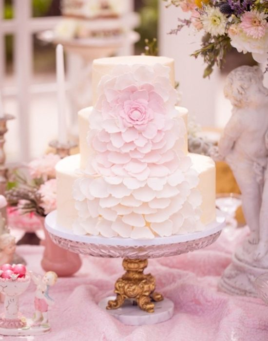 Pastel de bodas con pétalos de rosa cayendo
