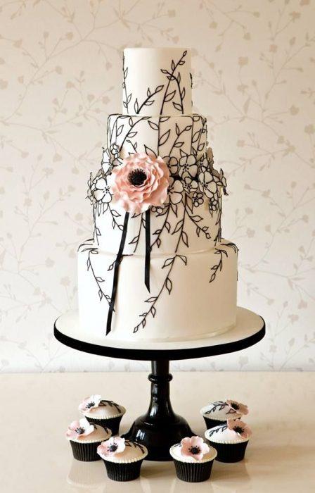 Pastel de bodas en color blanco con flores negras con rosa