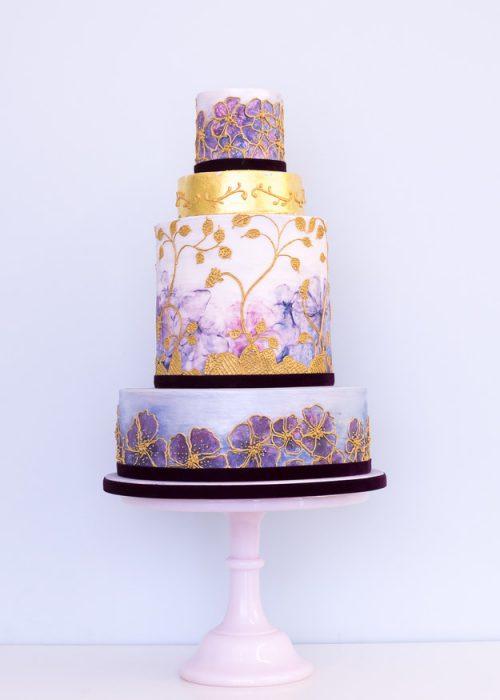 Pastel de odas en color morado con figuras en color dorado, morado y azul