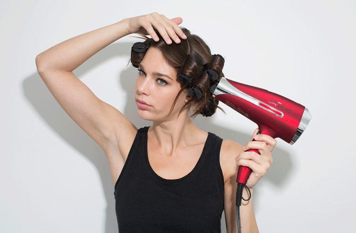 Chica tratando de rizar su cabello
