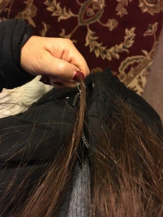 Chica con el cabello largo atorado en el ziper de una chamarra