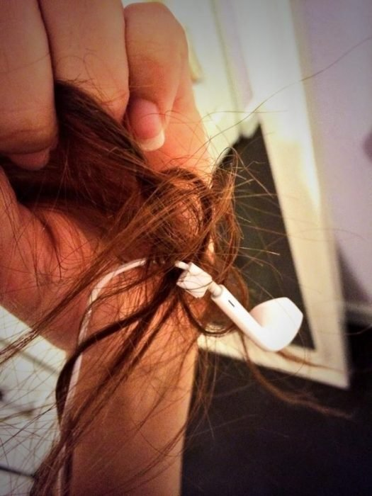 Audífonos enredados en el cabello de una chica