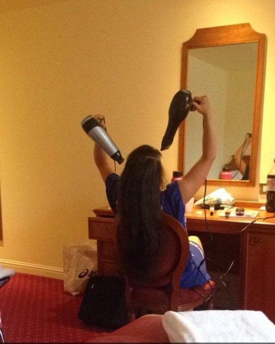 Chica secando su cabello con dos secadoras