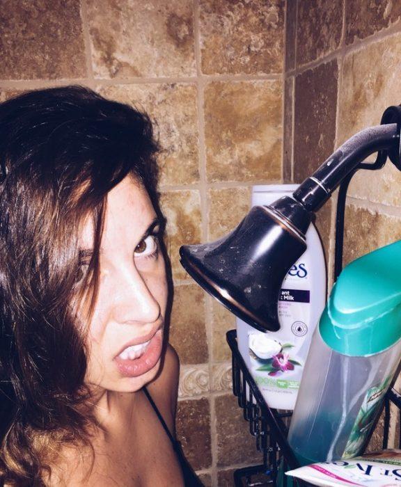 Chica alta tratando de tomar una ducha