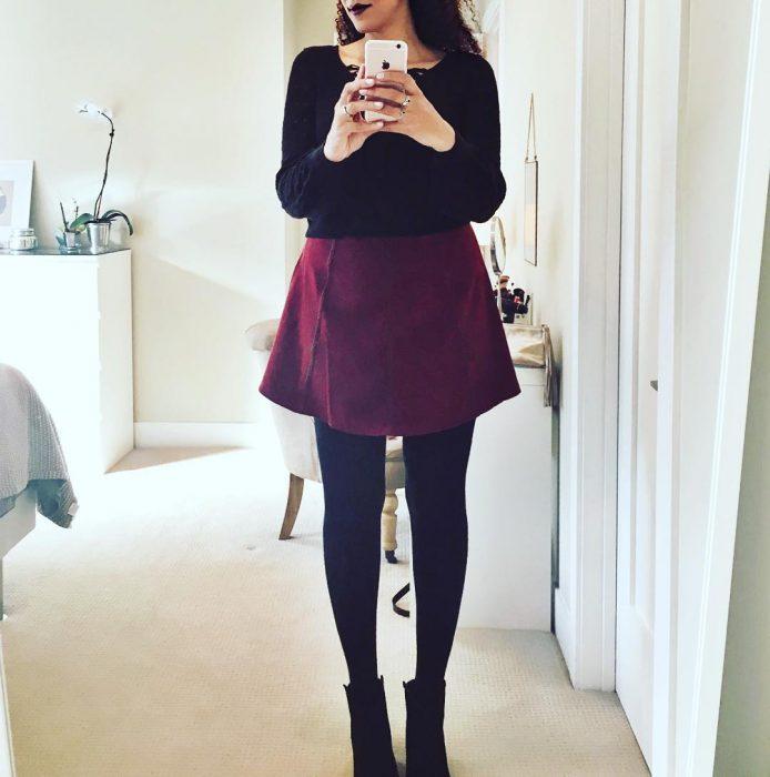 Chica alta tratando de verse en un espejo