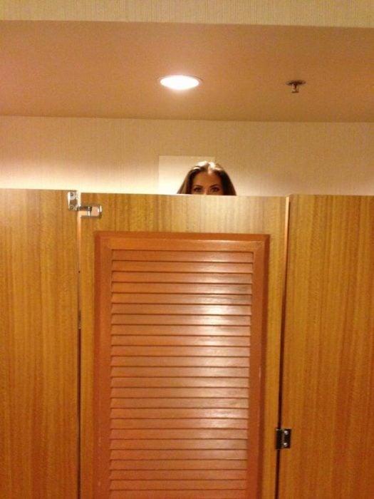 Chica alta con la cabeza fuera de un probador
