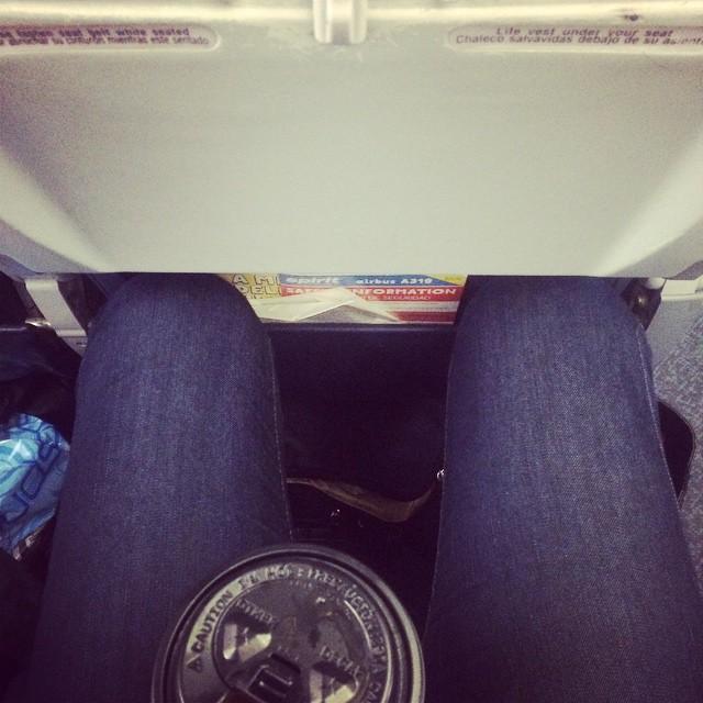 Chica alta con los pies atorados entre los asientos