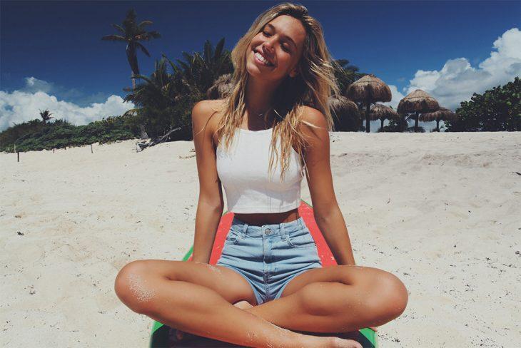 mujer sentada en la arena playa feliz rubia