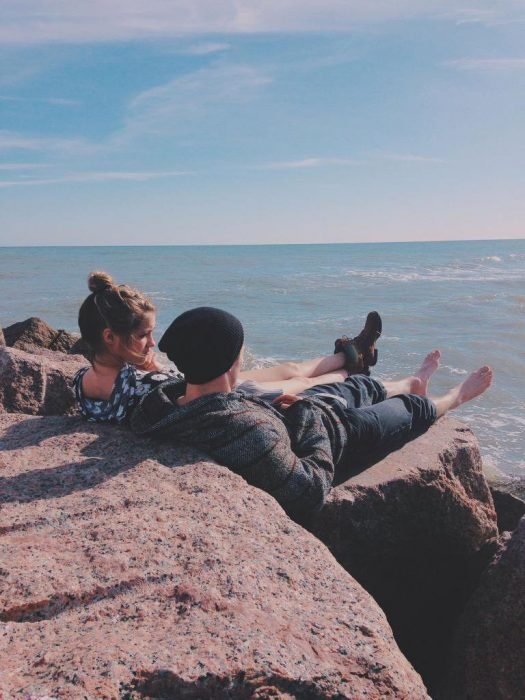 Pareja platicando en unas rocas frente a la playa