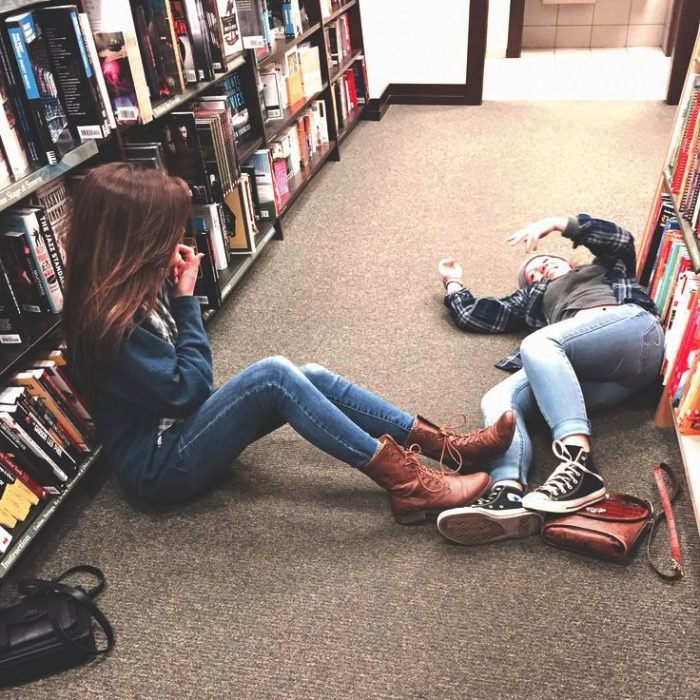 Chicas en una biblioteca recostadas en el suelo