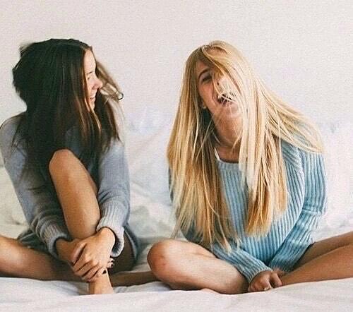 Chicas sentadas en la cama riendo