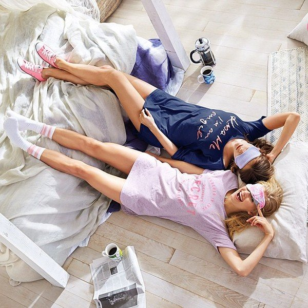 Chicas recostadas en una cama mientras usan pijamas