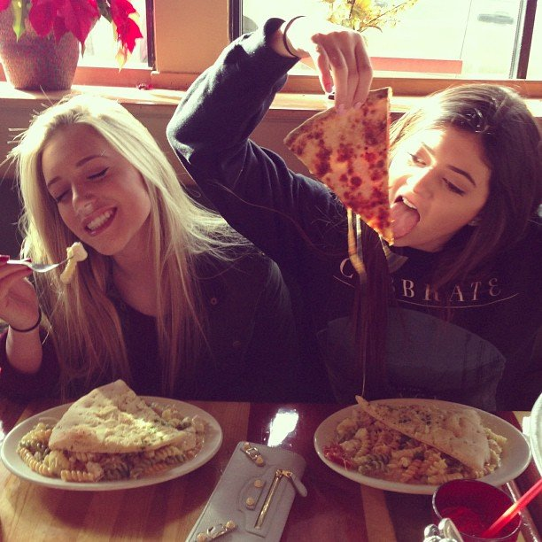 Chicas sentadas en la mesa de un restaurante comiendo pizza
