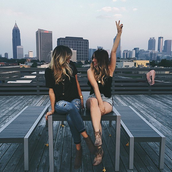 Chicas sentadas en la banca de un parque mientras están conversando