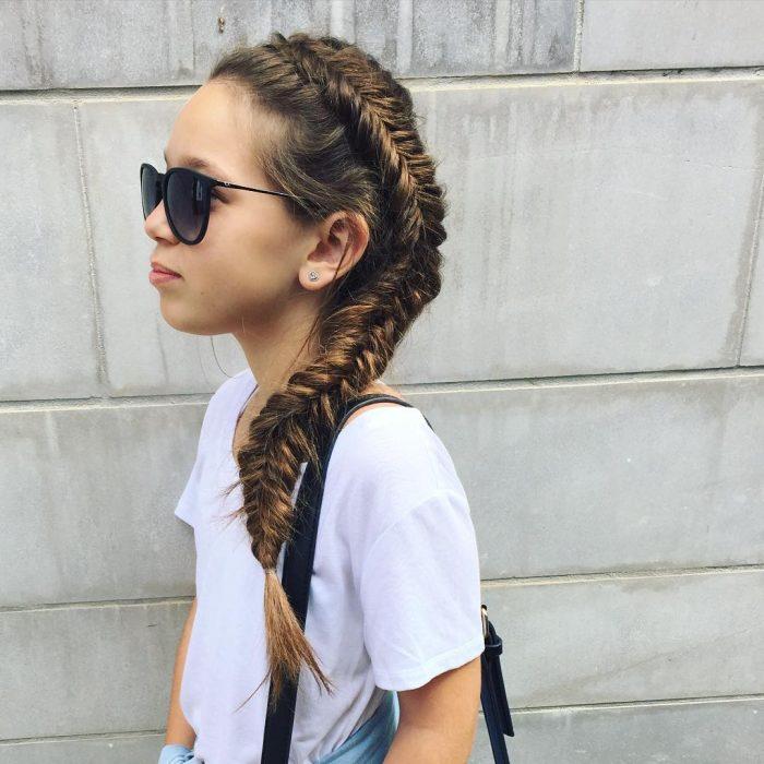 Chica con una trenza cola de pez que está en todo su cabeza