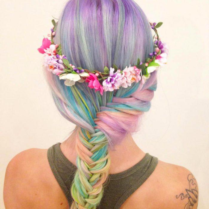 Chica con el cabello de colores y una trenza cola de pez adornada con flores
