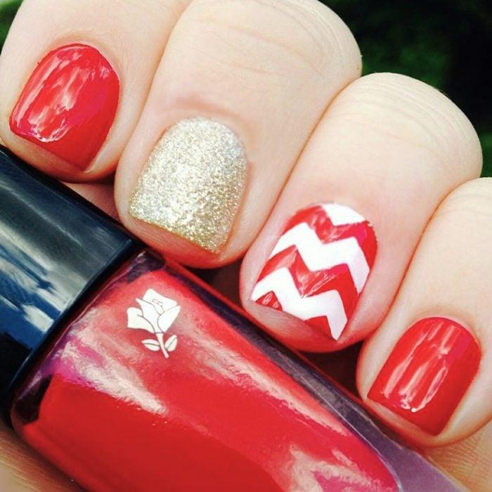 Uñas de color rojo con líneas blancas y doradas