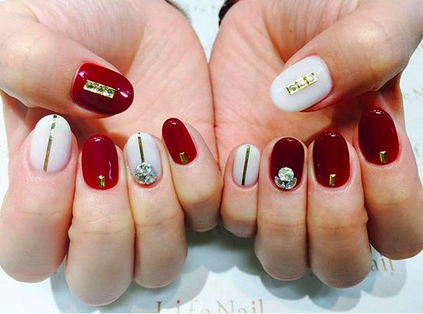 Uñas de color rojo con pedrería en color dorado