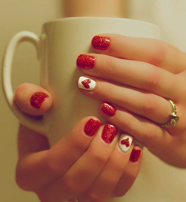 Uñas de color rojo con corazones en color blanco