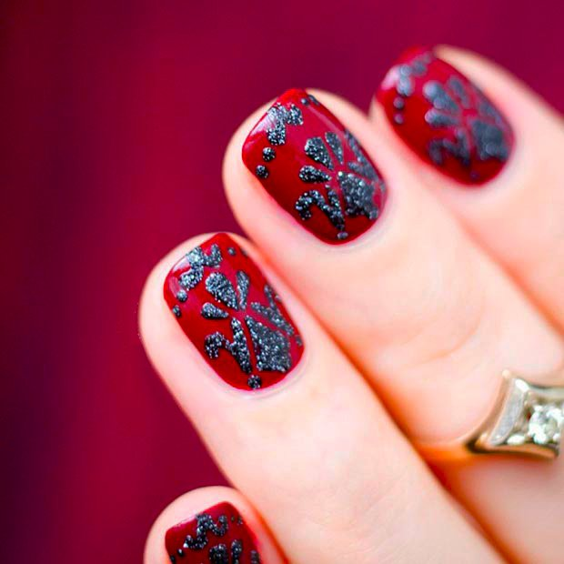 Uñas de color rojo con diseños en color negro