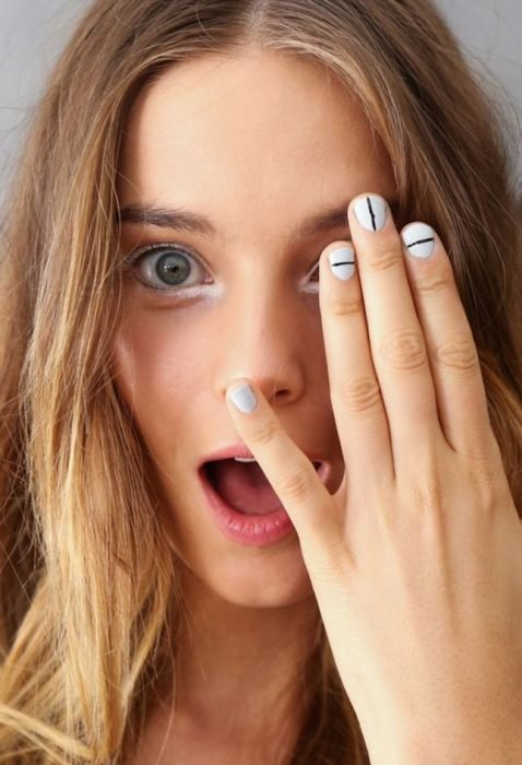 Uñas con diseños minimalistas en color blanco con lineas en color negro