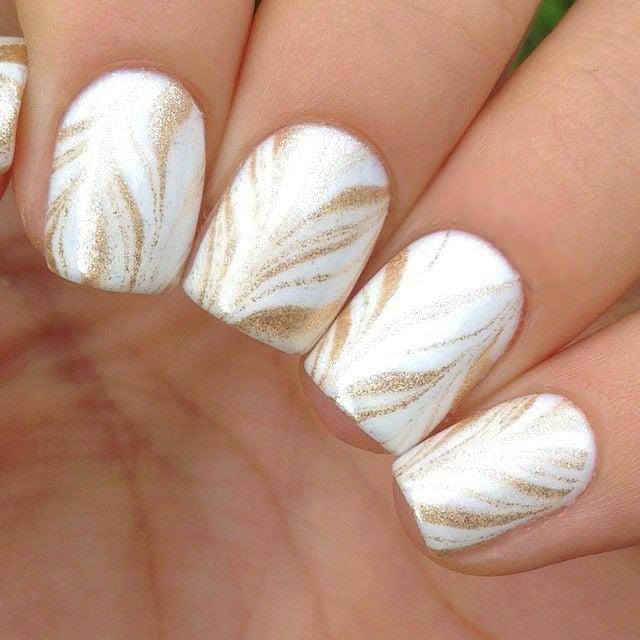 Uñas con diseños minimalistas en color blanco con líneas en color dorado
