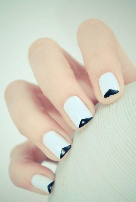 Uñas con diseños minimalistas en color blanco con la punta nen color negro