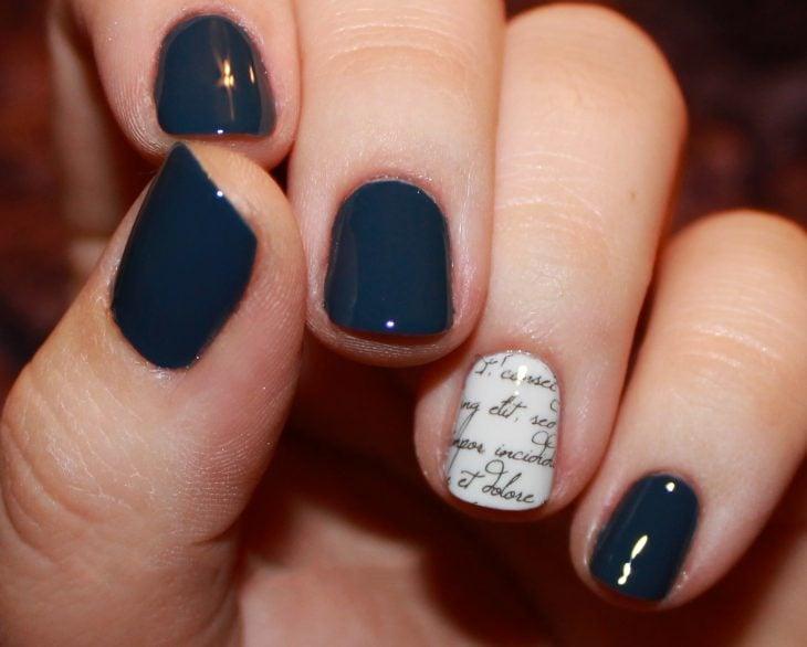 Uñas con diseños minimalistas en color azul con una uña en blanco con letras en negro