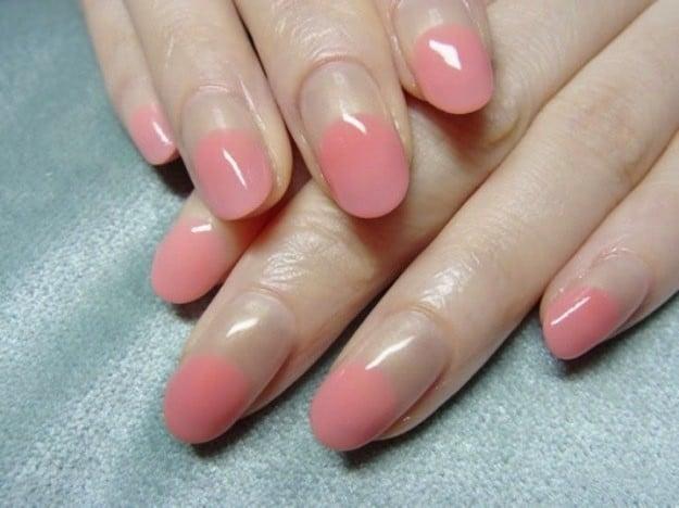 Uñas con diseños minimalistas con la mitad de la uña en color rosa