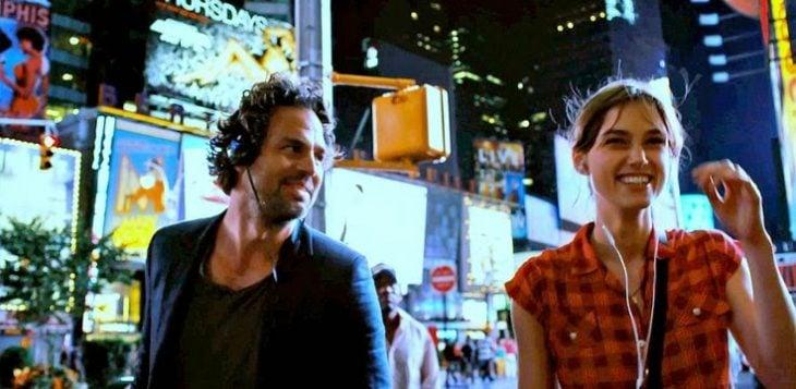 pareja caminando de noche escuchan la misma cancion