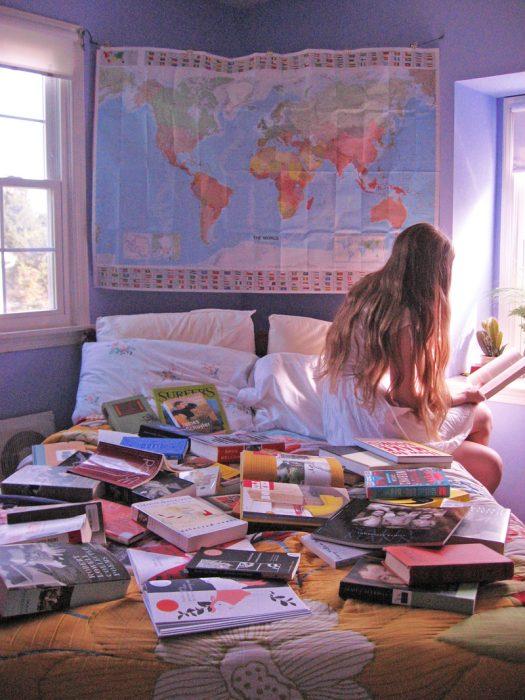 mujer sentada cama libros leyendo