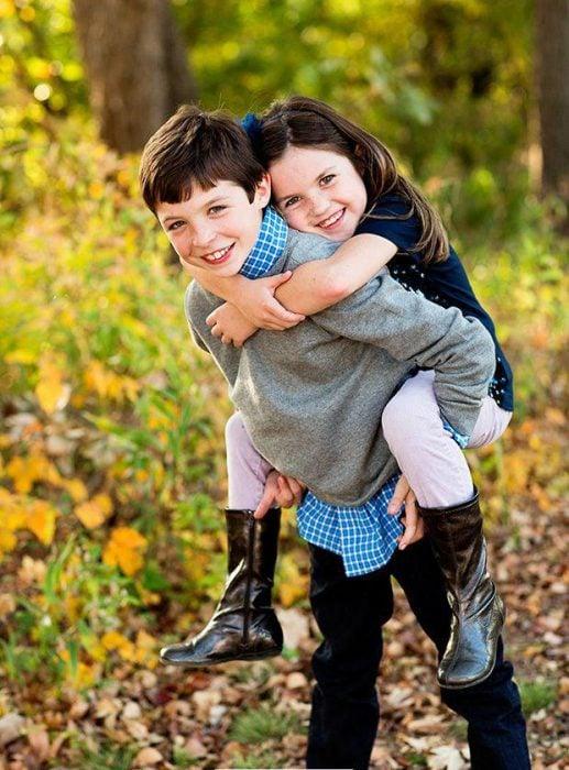 Niño cargqando a su hermana en la espalda