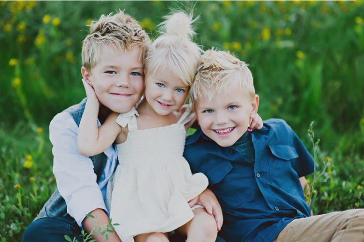 Hermanos abrazándose mientras están sentados en el pasto