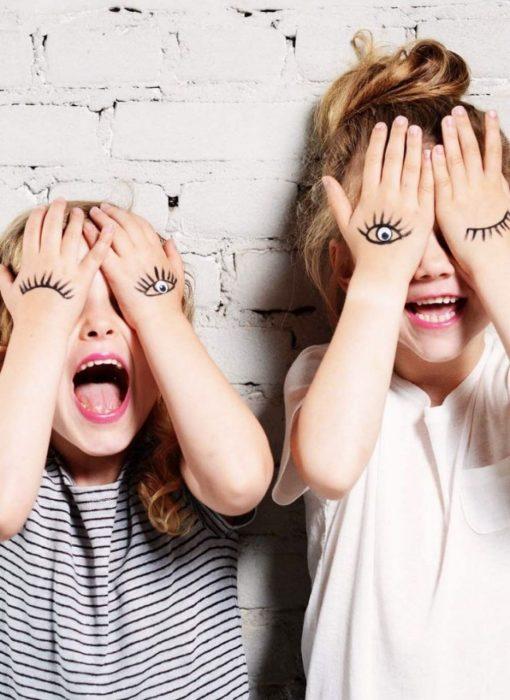 Hermanas con las manos pintadas en dorma de ojos mientras las ponen sobre su cara