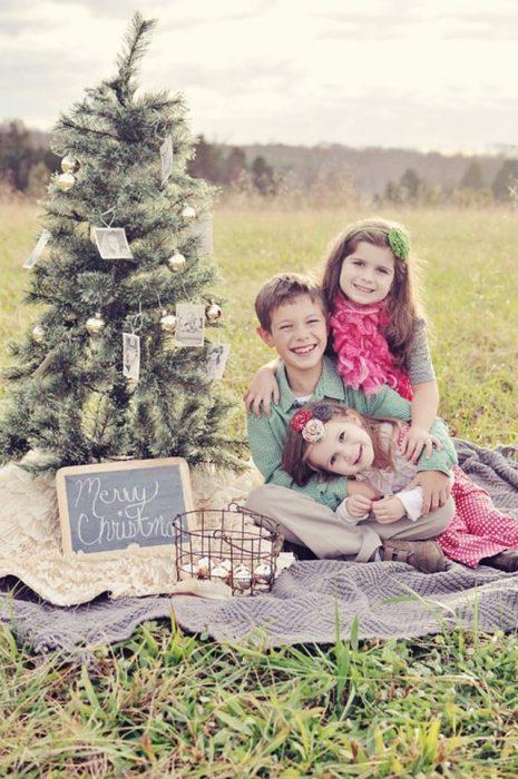 Hermanos sentados en el pasto junto a un árbol abrazados